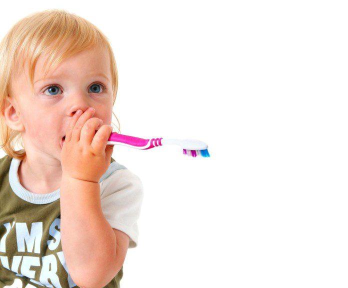 criança com escova de dentes